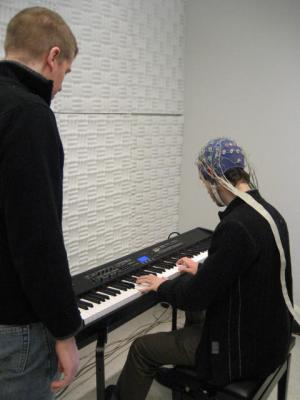 For the study, researchers recruited twenty skilled pianists from Lyon, France. The group was asked to learn simple melodies by either hearing them several times or performing them several times on a piano. Pianists then heard all of the melodies they had learned, some of which contained wrong notes, while their brain electric signals were measured using electroencephalography (EEG). Credit: Caroline Palmer/Brian Mathias